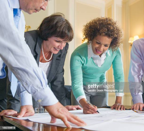 Business people reading blueprints in meeting