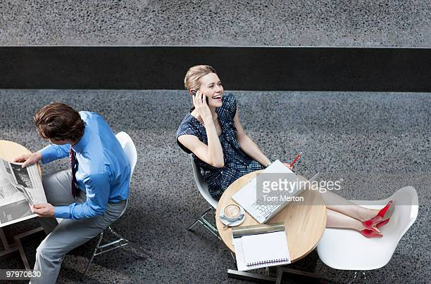 Business people reading newspaper and using cell phone at tables