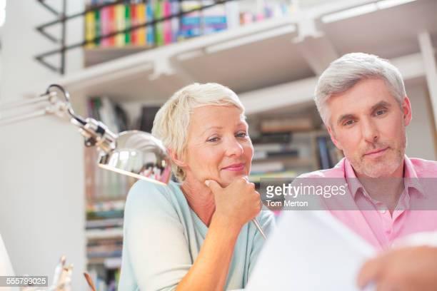 Business people reading paperwork in office meeting