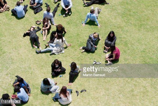 Business people relaxing in sunny field : Stock Photo