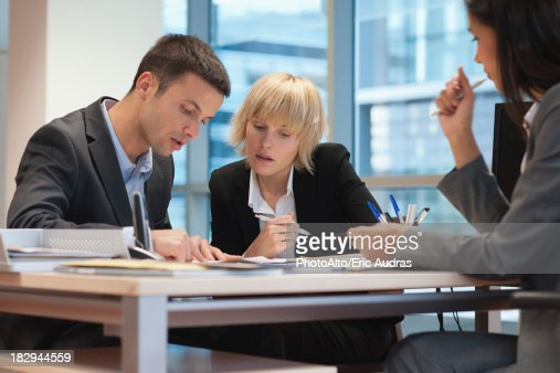 Business people reviewing contract while meeting with female excutive