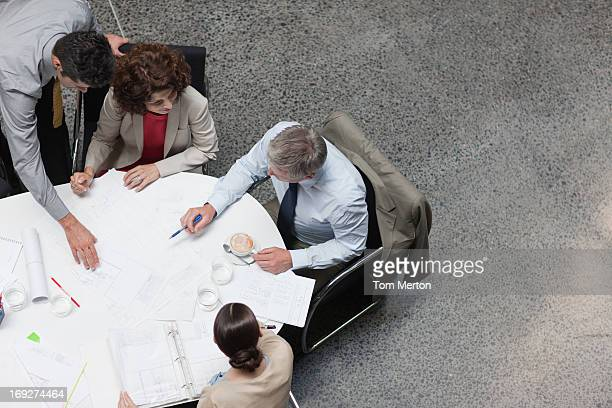 Business people reviewing paperwork at conference table