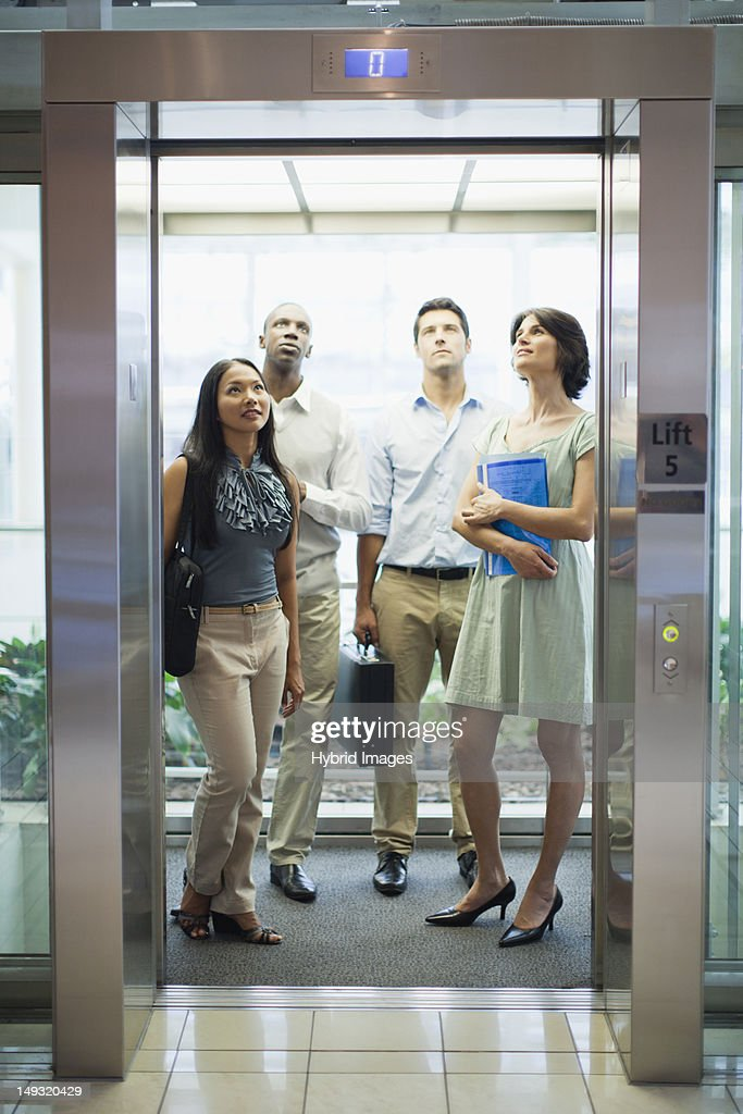 Business people riding glass elevator : Stock Photo