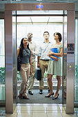 Business people riding glass elevator