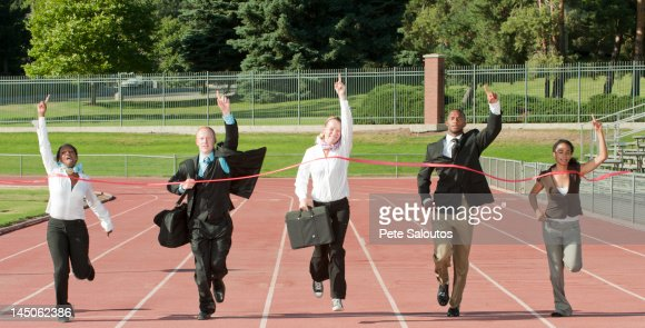 Business people running across track finish line : Foto de stock