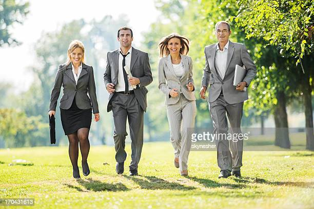 Business people running in park