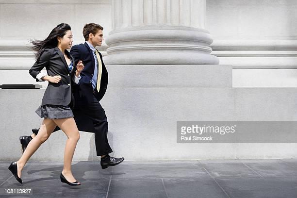 Business people running on sidewalk