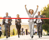 Business people running to finish, crossing red line.