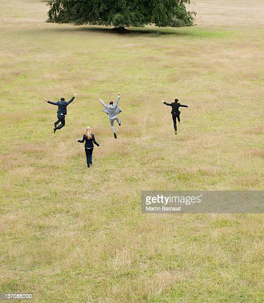 Business people running together in field