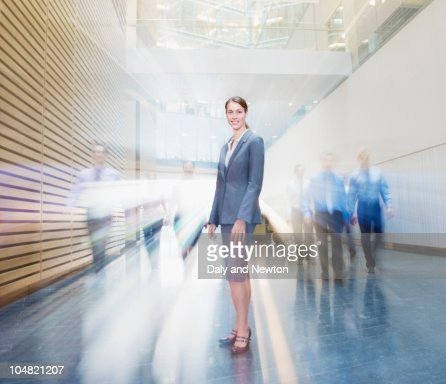 Business people rushing past smiling businesswoman in lobby