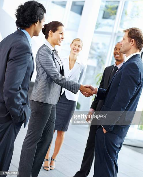 Business people shaking hands and smiling in suits