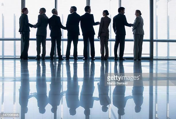 ビジネスの人々の手を振る列のロビーの窓