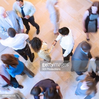 Business people shaking hands in busy crowded lobby