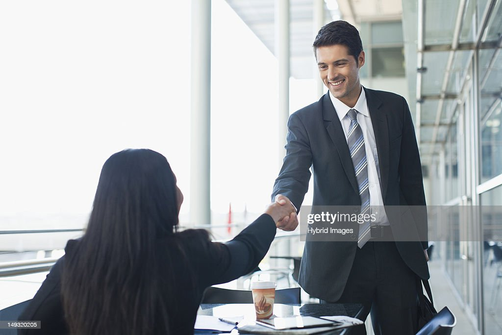 Business people shaking hands in cafe : Stock Photo