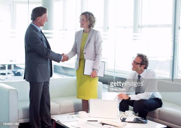 ビジネスの人々の手を振るオフィスのロビーエリア