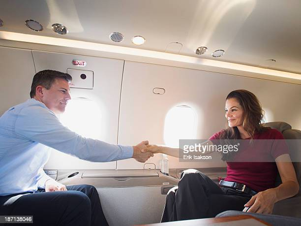 Business people shaking hands on airplane