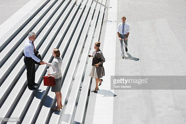 Business people shaking hands on stairs