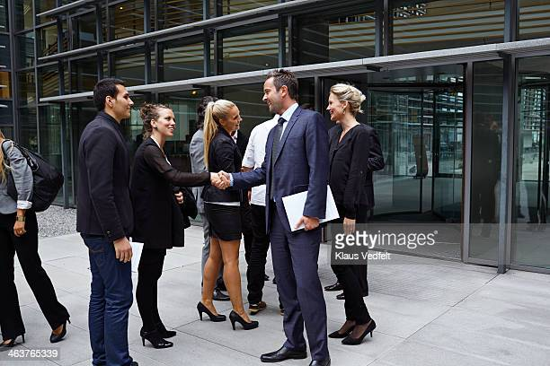 Business people shaking hands outside corporation
