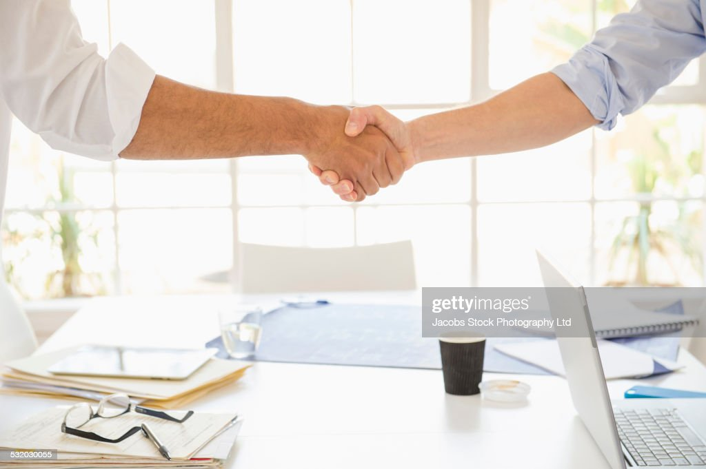 Business people shaking hands over conference table