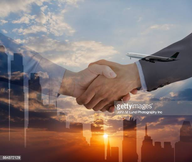 Business people shaking hands over silhouette of city skyline
