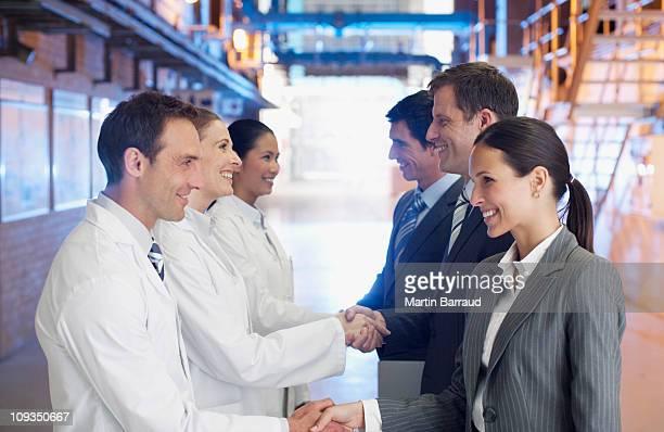 Geschäftsleute schütteln die Hände mit Wissenschaftler in Fabrik