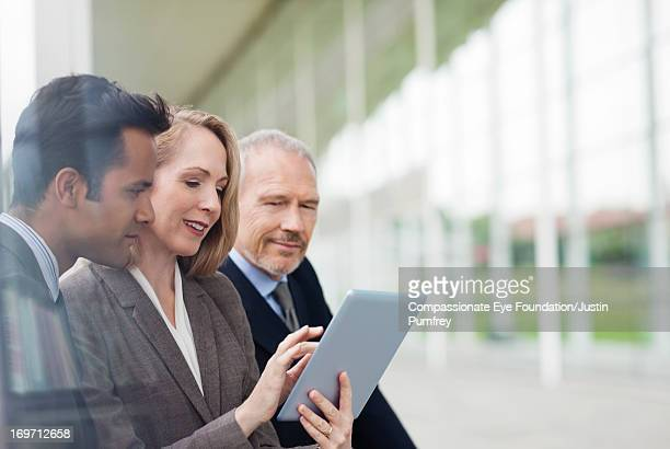 Business people sharing digital tablet outdoors