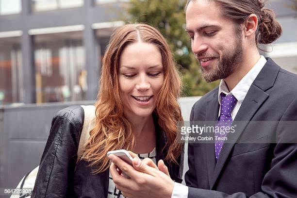 Business people sharing information on smartphone, New York, USA