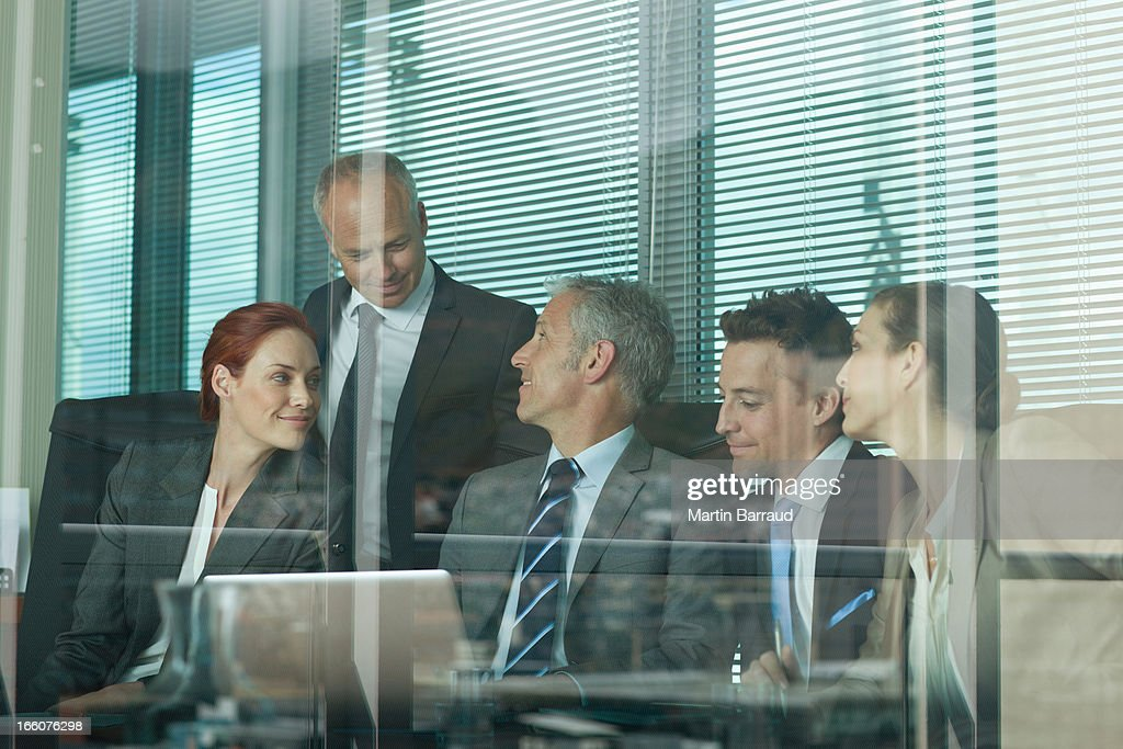 Business people sharing laptop in meeting : Stock Photo
