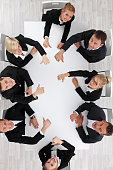Business people showing thumbs up sitting around white conference table in office