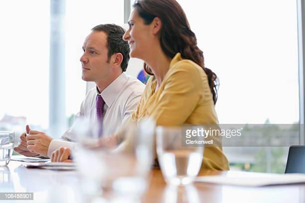 Geschäftsleute sitzen um Konferenztisch im Büro