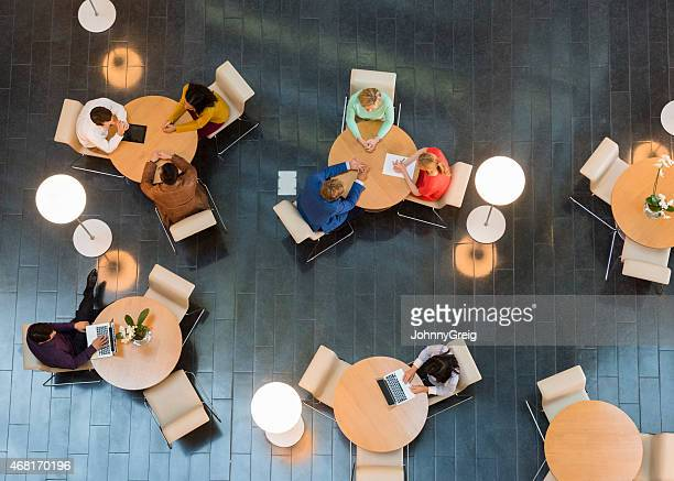 Business people sitting at tables in office lobby