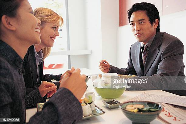Business People Sitting Enjoying a Meal in a Japanese Restaurant