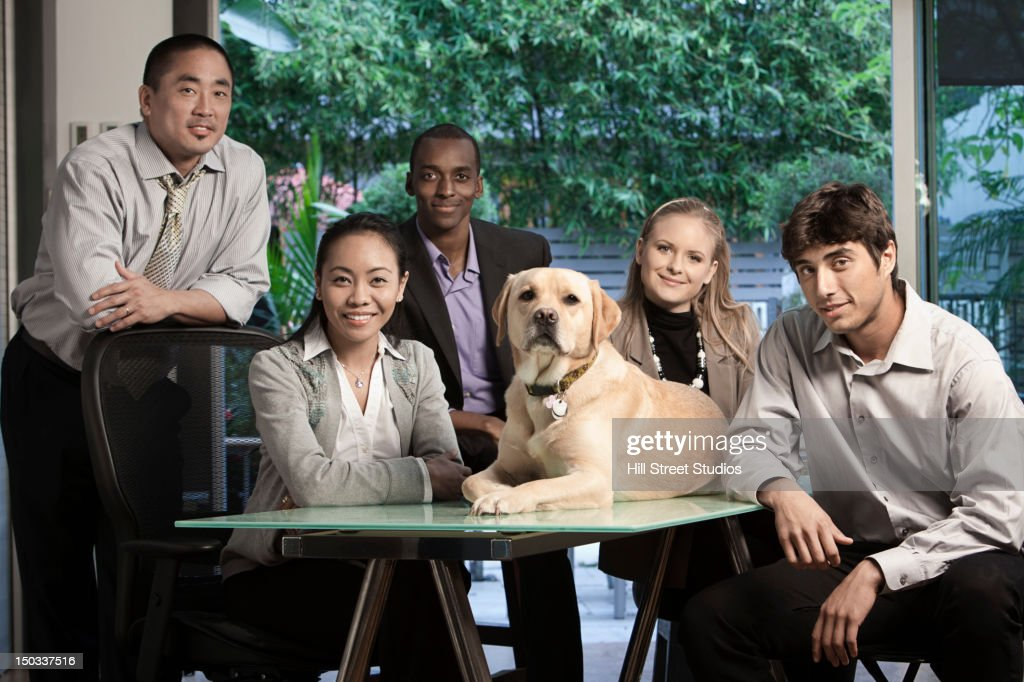 Business people sitting in conference with dog : Stock Photo
