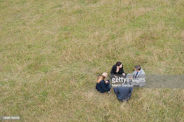 Business people sitting in grass together outdoors