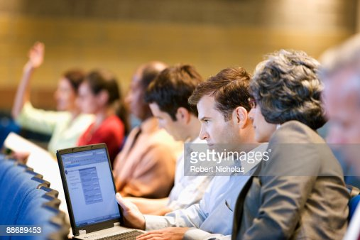 Business people sitting in lecture hall with laptop : Stock Photo