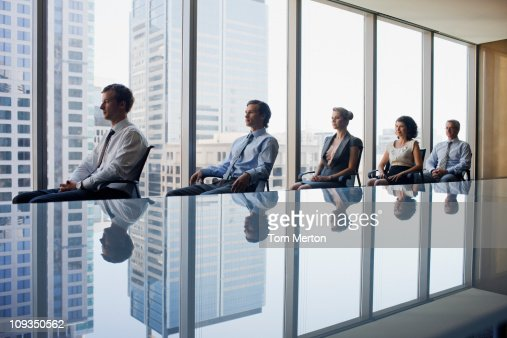 Business people sitting in row together in conference room : Stock Photo