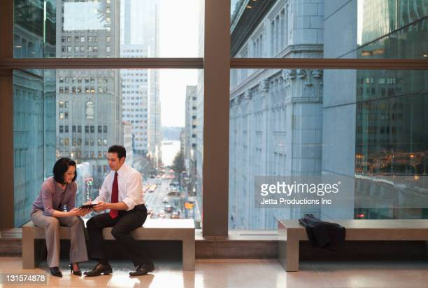 Business people sitting on bench looking at digital tablet