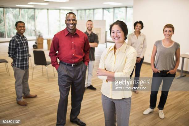 Business people smiling in empty office