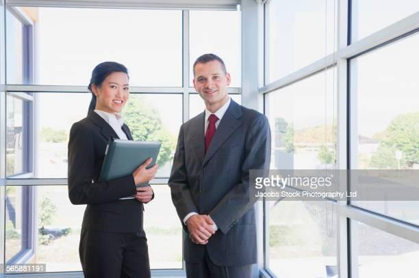 Business people smiling near office window