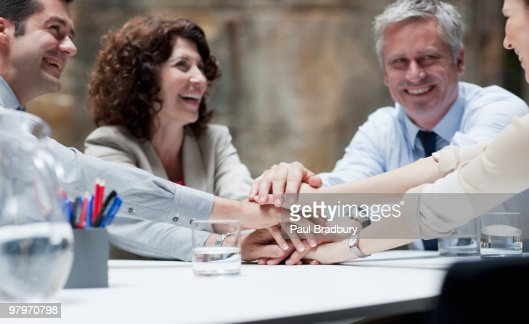 Business people stacking hands in meeting : Stock Photo