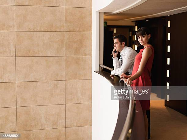 Business people standing at balcony in hotel corridor