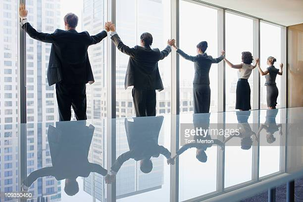 Business people standing at conference room window holding hands