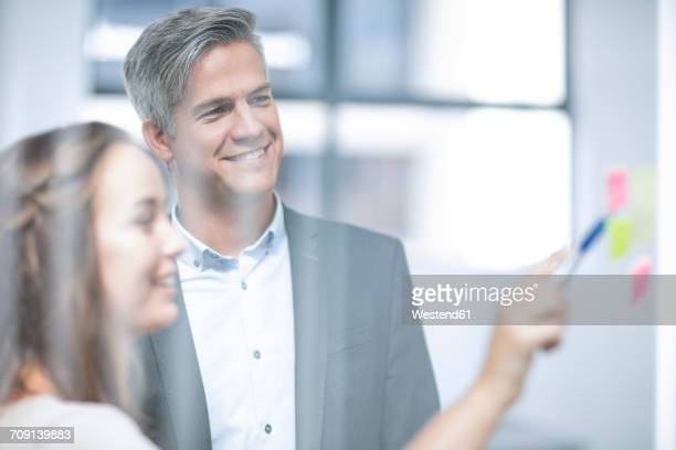 Business people standing by glass pane, brainstorming