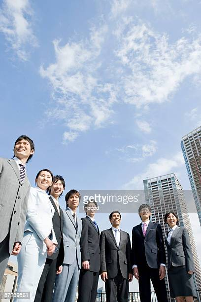 Business people standing in a row, smiling