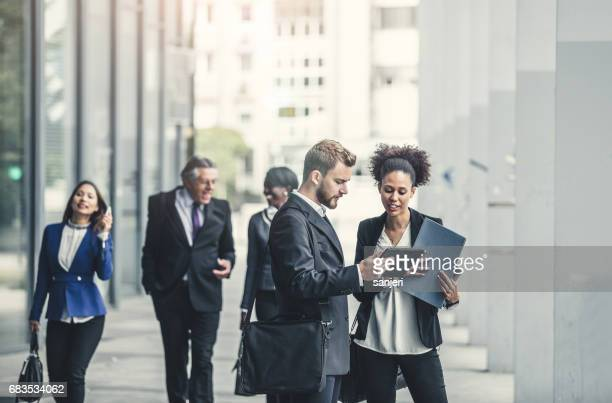 Business People Standing in Street and Discussing
