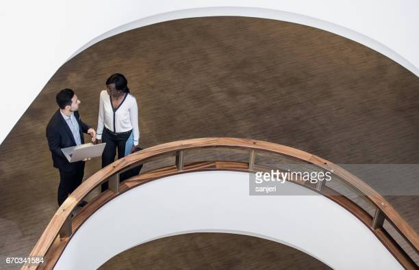 Business People Standing in the Middle of a Building's Corridor, Discussing and Using Laptop