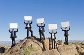 Business people standing on rocks holding placards