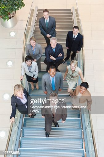 Business people standing on stairs in lobby : Stock Photo