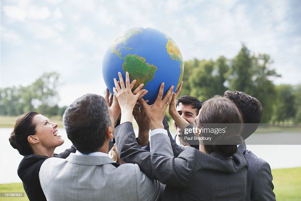 Business people standing outdoors holding globe together : Stock Photo