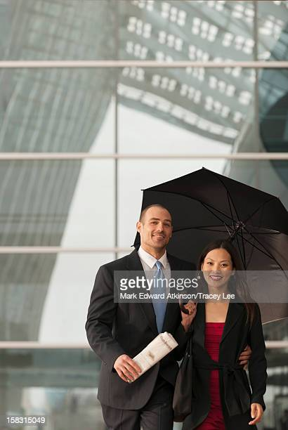 Business people standing together with umbrella
